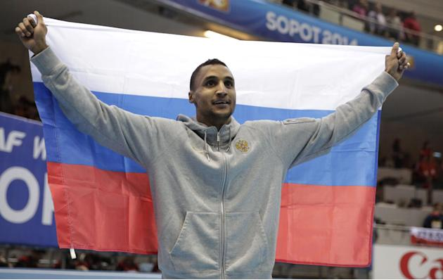 Russia's Lyukman Adams holds the Russian flag as he celebrates winning the gold medal of the men's triple jump during the Athletics Indoor World Championships in Sopot, Poland, Sunday, March 9