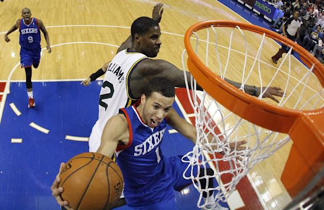 Philadelphia 76ers' Michael Carter-Williams (1) goes up to shoot against Utah Jazz's Marvin Williams (2) during the first half of an NBA basketball game on Saturday, March 8, 2014, in Philadel