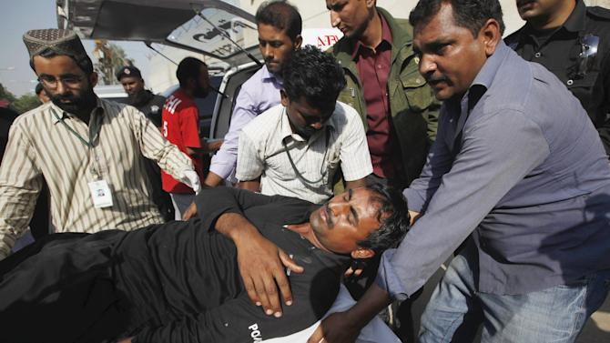 Men move an injured SSU soldier outside a hospital, after he was wounded with others from an explosion near their vehicle, in Karachi