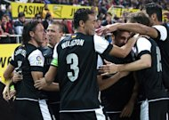 Malaga&#39;s Martin Demichelis (L) celebrates with teammates after scoring a goal against Sevilla during their Spanish La Liga match at the Ramon Sanchez Pizjuan stadium in Sevilla, on December 15, 2012. Malaga won 2-0