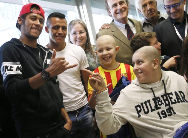 Barcelona's Neymar and Alexis Sanchez joke with children during a charity visit to the Hospital Sant Joan de Deu in Barcelona