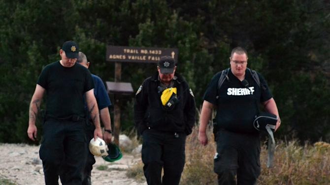 Chaffee County Sheriff's Deputy Kevin Everson, right, and other deputies walk out the Agnes Vaille Falls trail shortly after leaving the scene of a rock slide that killed five people Monday, Sept. 30, 2013, in Chaffee County, Colo. Deputies who reached the area rescued a teenage girl who suffered a broken leg but had to pull back after rocks kept falling from a cliff and a boulder field with rocks estimated at weighing more than 100 tons began shifting. Rescuers were to return to the site Wednesday. (AP Photo/P. Solomon Banda)