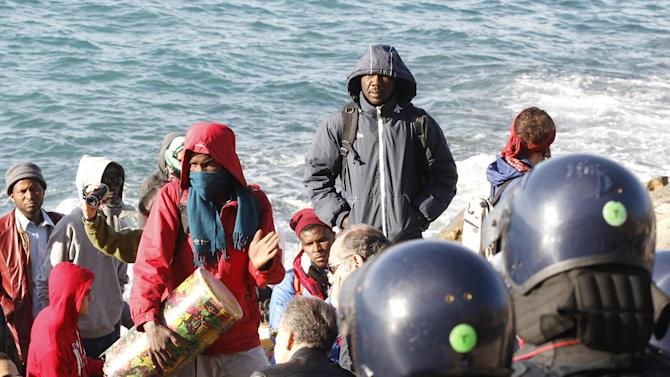 Refugees and migrants face Italian police officers in riot gear at the Franco-Italian border in Ventimiglia, Italy, Wednesday, Sept. 30, 2015. Italian police have emptied out a migrant tent camp in the border city of Ventimiglia, prompting dozens of migrants to flee to rocks along the shoreline. (AP Photo/Lionel Cironneau)
