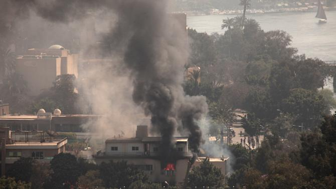 Smoke and fire rises from the Egyptian Soccer Federation after protesters set fire following a court verdict in, Cairo, Egypt, Saturday, March 9, 2013. Fans of Cairo's Al-Ahly club have stormed Egypt's soccer federation headquarters, set it ablaze after a court acquitted seven of nine police official on trial for their alleged part in deadly stadium melee. A fire also broke out Saturday in a nearby police club, but it was not immediately known whether Al-Ahly fans started the blaze there too. (AP Photo/Maya Alleruzzo)