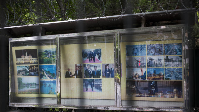 A billboard displays photos, from left, of Vietnam's tourism scenic, Chinese and Vietnamese state leaders official visit and Industrial factories, placed outside the Vietnamese embassy in Beijing Wednesday, May 14, 2014. Anti-China mobs torched up to 15 foreign-owned factories and trashed many more in southern Vietnam amid rising anger over China's recent placement of an oil rig in disputed Southeast Asian waters, officials and state media said Wednesday. (AP Photo/Andy Wong)