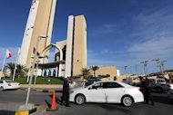 Security officials check a vehicle outside the Corinthia hotel in Tripoli on October 10, 2013