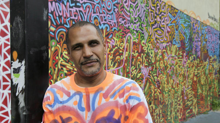 "In this Friday, July 27, 2012 photo, graffiti artist Angel ""LA II"" Ortiz poses for photos with one of his creations, in a schoolyard on New York's Lower East Side. A number of New York's graffiti artists of the 1970s and '80s still have the urge to tag. (AP Photo/Richard Drew)"