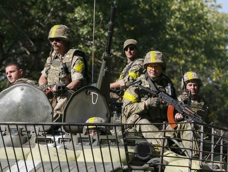 Ukrainian servicemen ride in an armoured vehicle near Kramatorsk