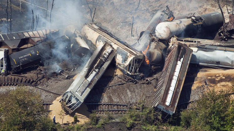 FILE - This July 11, 2012 aerial file photo, a freight train is seen after an early morning derailment in Columbus, Ohio. Part of the freight train carrying ethanol derailed and caught fire, shooting flames skyward into the darkness and prompting the evacuation of a mile-wide area as firefighters and hazardous materials crews monitored the blaze. For two decades, one of the nation's most common types of rail tanker, known as a DOT-111, a workhorse of the American rail fleet, has been allowed to haul hazardous liquids from coast to coast even though transportation officials were aware of a dangerous design flaw that almost guarantees the car will tear open in an accident. The rail and chemical industries have committed to a safer design for new tankers, but they do not want to modify tens of thousands of existing cars. That's despite a spike in the number of accidents. (AP Photo/The Columbus Dispatch, Eamon Queeney)  MANDATORY CREDIT