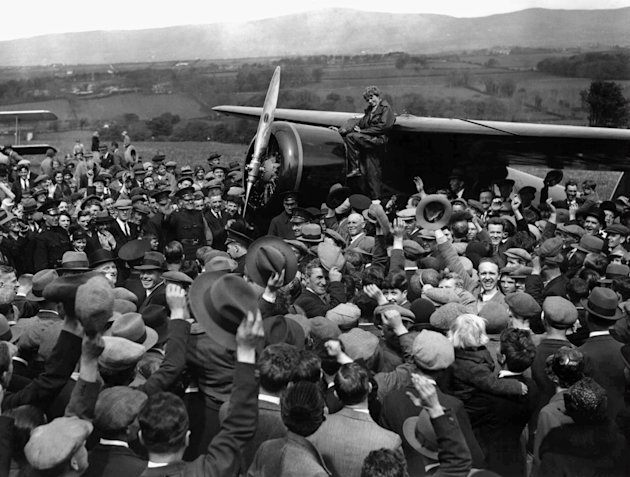 FILE - In this May 22, 1932 file photo, a crowd cheers Amelia Earhart as she boards her single-engine Lockheed Vega airplane in Londonderry, Northern Ireland, for the trip back to London. Three bone f
