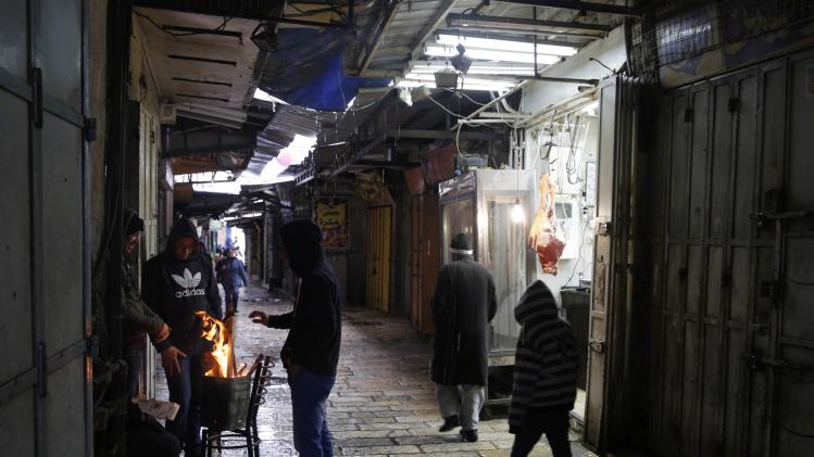People warm themselves near a fire in a market in Jerusalem's Old City