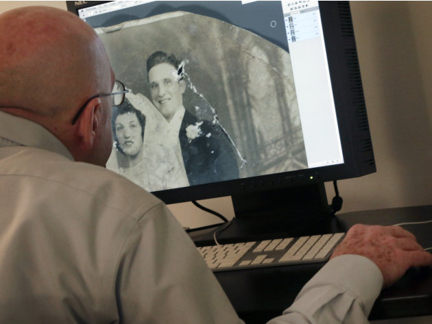 In this Saturday, Feb. 2, 2013 image, photo restorer Dennis McKeever uses Photoshop to retouch a damaged photo belonging to Florence Catania, of Deer Park, N.Y., during the restoration project of Oper