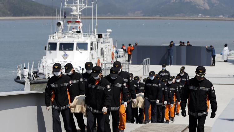 South Korean rescue workers carry the bodies of passengers who were on the capsized passenger ship at a port in Jindo