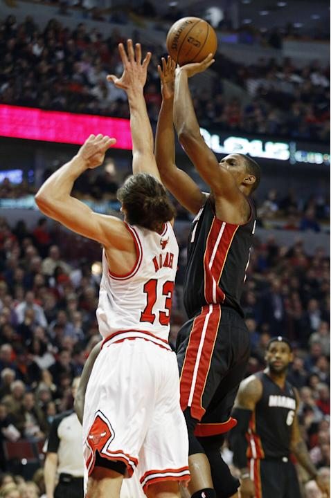 Miami Heat center Chris Bosh, right, shoots over Chicago Bulls center Joakim Noah, left, during the first half of an NBA basketball game in Chicago, Thursday, Dec. 5, 2013