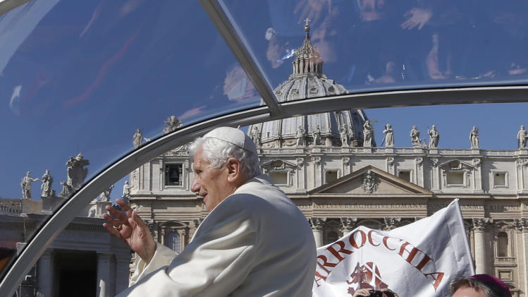 """Faithful are reflected in the roof of Pope Benedict XVI's pope-mobile as he arrives with his personal secretary Archbishop Georg Gaenswein, right, for his last general audience in St. Peter's Square, at the Vatican, Wednesday, Feb. 27, 2013. Benedict XVI basked in an emotional sendoff Wednesday at his final general audience in St. Peter's Square, recalling moments of """"joy and light"""" during his papacy but also times of great difficulty. He also thanked his flock for respecting his decision to retire. (AP Photo/Alessandra Tarantino)"""