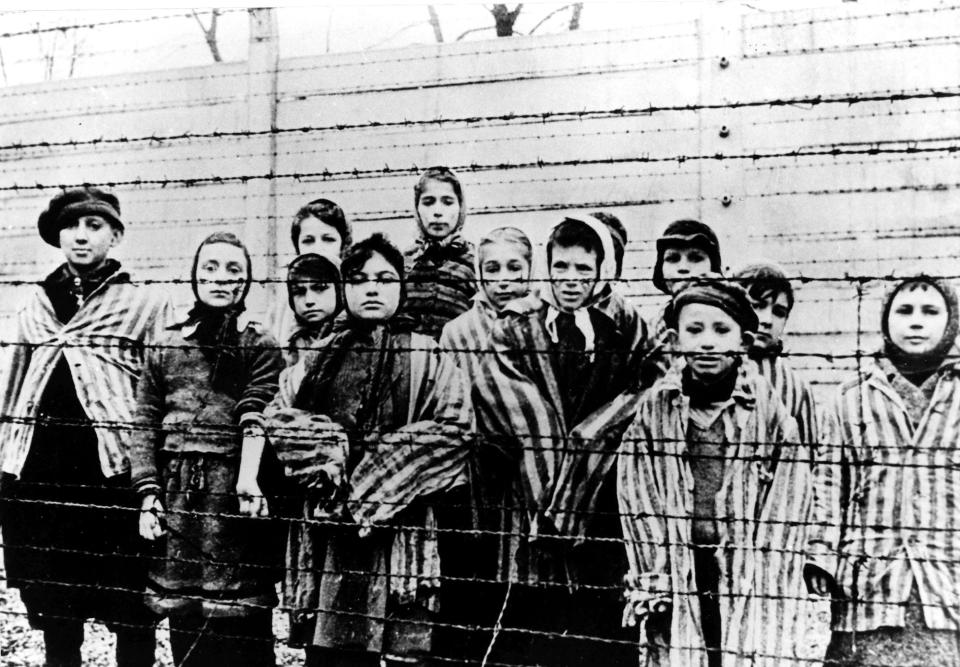 A picture taken just after the liberation by the Soviet army in January, 1945, shows a group of children wearing concentration camp uniforms behind...