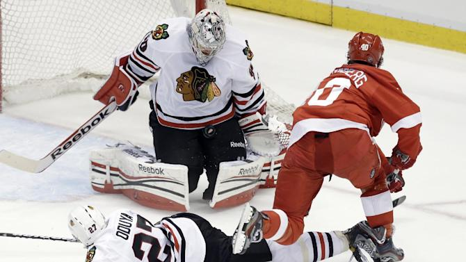 Chicago Blackhawks goalie Corey Crawford (50) stops shot by Detroit Red Wings center Henrik Zetterberg (40), of Sweden, as defenseman Johnny Oduya (27), of Sweden, defends during the second period of an NHL hockey Stanley Cup playoffs Western Conference semifinal game in Detroit, Monday, May 20, 2013. (AP Photo/Paul Sancya)