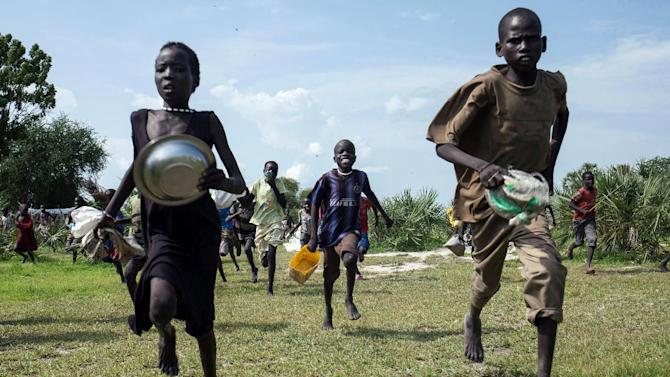 Children race onto the drop zone after an air drop by the International Red Cross in Leer, South Sudan, on July 5, 2014