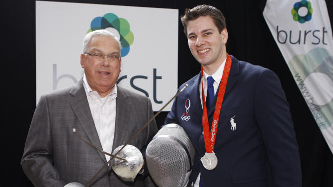 "COMMERCIAL IMAGE -  In this photograph taken by AP Images for Burst, U.S. Olympic fencer Tim Morehouse, right, who will use mobile video solution Burst during this summer's Olympic Games, stands with Boston Mayor Thomas M. Menino during the unveiling of the ""Burst from Behind the Scenes in London"" program, hosted by Boston start-up Burst and Boston Properties, at the Shops at the Prudential Center, Thursday, July 5, 2012, in Boston.  (Bizuayehu Tesfaye/AP Images for Burst)"