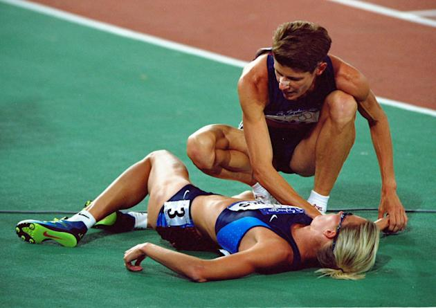 30 Sep 2000: Marla Runyan of the USA helps compatriot Suzy Favor Hamilton after the Womens 1500m Final at the Olympic Stadium on day 15 of the Sydney 2000 Olympic Games in Sydney, Australia. \ Mandato
