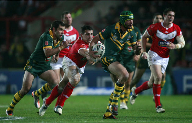 Australia's Johnathan Thurston, center, is tackled by Wales' Ben Flower, third left, during their four nations rugby league test match at the Racecourse Ground, Wrexham, Wales, Sunday Nov. 13, 2011. (
