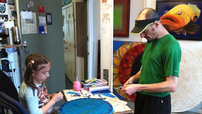 This April 19, 2015 photo shows Stephen Lange and his daughter, Esme, 10, working in his studio in the River Arts District of Asheville, N.C. Lange's unusual works are made from brightly colored tape arranged in intricate geometic patterns on birch wood. He's one of more than 180 artists working in the River Arts District. (AP Photo/Beth J. Harpaz)