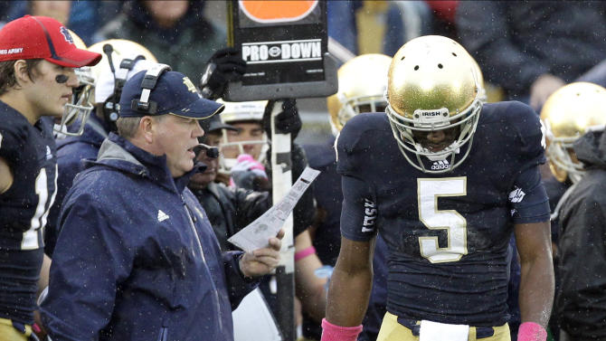 FILE- In this Oct. 13, 2012, file photo, Notre Dame quarterback Everett Golson (5) looks down as coach Brian Kelly looks over his play card during the first half of an NCAA college football game against Stanford in South Bend, Ind. Golson's high school coach says he believes the quarterback will learn from being suspended by Notre Dame for the fall semester. (AP Photo/Nam Y. Huh, File)