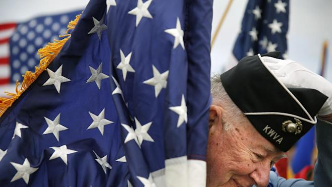 Korean War veteran Bob Pellow, 84, a flag bearer, puts his hat back on after strong winds knocked it off during Memorial Day ceremonies at the State Veterans Cemetery in Little Falls, Minn., Sunday, May 26, 2013. (AP Photo/The Star Tribune, Richard Tsong-Taatarii)