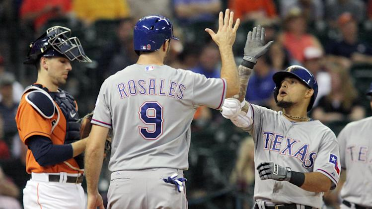 Texas Ranger's Rougned Odor, right, celebrates his three-rum home run with Adam Rosales as Houston Astros catcher Jason Castro stands by in the seventh inning of a baseball game Friday, Aug. 29, 2014, in Houston. (AP Photo/Richard Carson)