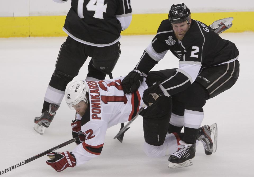 New Jersey Devils left wing Alexei Ponikarovsky (12) hits the ice as he gets tangled up with Los Angeles Kings defenseman Matt Greene (2) in the first period during Game 3 of the Stanley Cup Finals, Monday, June 4, 2012, in Los Angeles.  (AP Photo/Jae C. Hong)