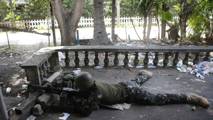 A government soldier takes a position with a machinegun at the porch of a house during fighting with Muslim rebels from the MNLF in Zamboanga city, southern Philippines
