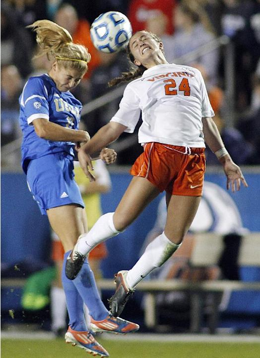 UCLA's Rosie White, left, battles Virginia's Danielle Colaprico for the ball during the second half of an NCAA college soccer semifinal match at the Women's College Cup soccer tournament i
