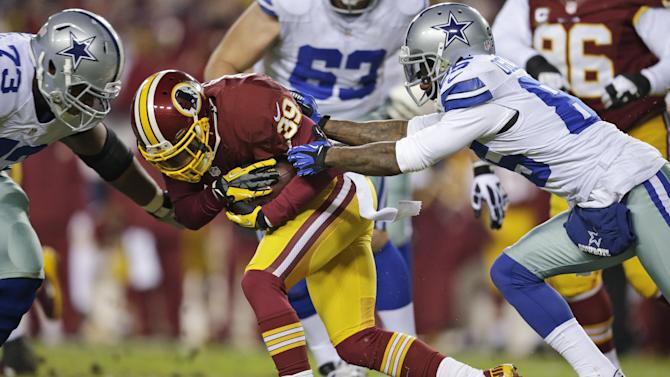Washington Redskins cornerback Richard Crawford (39) is tackled, after his interception, by Dallas Cowboys guard Mackenzy Bernadeau (73) and wide receiver Kevin Ogletree (85) during the first half of an NFL football game Sunday, Dec. 30, 2012, in Landover, Md. (AP Photo/Evan Vucci)
