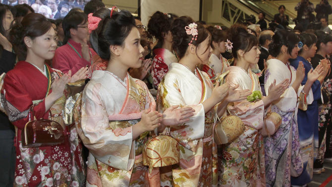 Kimono-clad workers clap their hands during the traditional New Year's opening ceremony of Tokyo Stock Exchange in Tokyo, Wednesday, Jan. 4, 2012. Asian stock markets were mostly higher Wednesday after Wall Street opened the year with a bang following the release of positive U.S. economic data. Japan's Nikkei 225 index gained 1.1 percent to 8,551.77. (AP Photo/Shizuo Kambayashi)