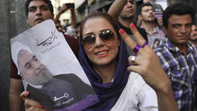 A female supporter of Iranian presidential candidate Hasan Rowhani flashes a victory sign as she holds his poster during a celebration gathering in Tehran, Iran, Saturday, June 15, 2013. Moderate cleric Hasan Rowhani was declared the winner of Iran's presidential vote on Saturday after gaining support among many reform-minded Iranians looking to claw back a bit of ground after years of crackdowns. (AP Photo/Vahid Salemi)