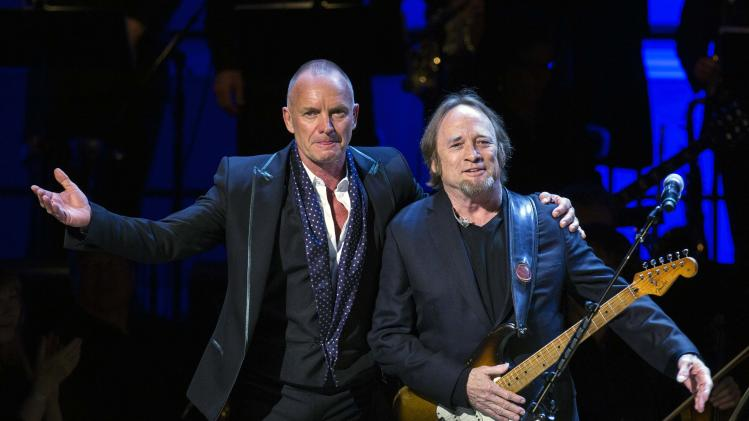 Singer Sting gestures next to Stephen Stills after a performance during the Rainforest Fund's 25th anniversary benefit concert in New York