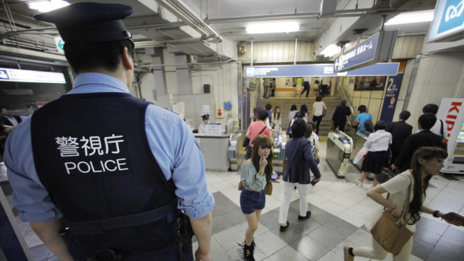 A police officer keeps eyes on people at a railway station in Tokyo, Friday, June 8, 2012. Thousands of police were mobilized Friday to hunt for the last fugitive suspected in a doomsday cult's deadly nerve gas attack on Tokyo's subway 17 years ago. Some 5,000 officers fanned out across the Tokyo area to hand out fresh photos of the fugitive, Katsuya Takahashi, and monitor transportation hubs to keep him from escaping the capital. (AP Photo/Itsuo Inouiye) (AP Photo/Itsuo Inouye)