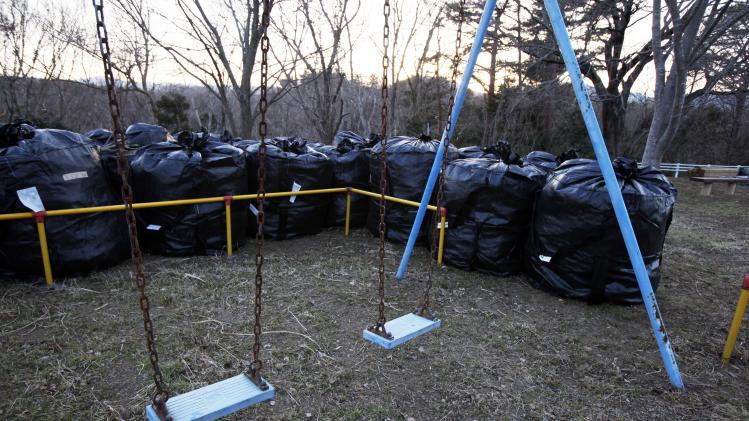 In this Tuesday, March 5, 2013 photo, bags of radiation-contaminated waste sit next to playground in the abandoned town of Naraha, just outside the exclusion zone surrounding the Fukushima Dai-ichi nuclear plant in Japan. Decontamination efforts have begun in the town but resident have not been allowed to return for more than brief visits. Two years after the triple calamities of earthquake, tsunami and nuclear disaster ravaged Japan's northeastern Pacific coast, radioactive and chemical contamination remains a threat as clean-up projects face troubles with organized crime and mishandling. (AP Photo/Greg Baker)