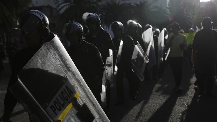 Riot policemen walk along a street next to demonstrators during a rally against the radical reform of the country's energy market in Mexico City