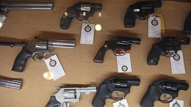 In this Jan. 4, 2013, photo, handguns are displayed in the sales area of Sandy Springs Gun Club and Range, in Sandy Springs, Ga. In Connecticut and Colorado, scenes of the most deadly U.S. mass shootings in 2012, people were less enthusiastic about buying new guns at the end of the year than in most other states, according to an Associated Press analysis of new FBI data. The biggest surges in background checks for people who want to carry or buy guns occurred in states in the South and West. (AP Photo/Robert Ray)