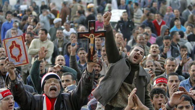Egyptian protesters shout anti-Muslim Brotherhood slogans during a demonstration marking the second anniversary of former President Hosni Mubarak's resignation, in Tahrir Square, Cairo, Egypt, Monday, Feb. 11, 2013. Egypt has witnessed a fresh cycle of violence over the past weeks since the second anniversary of the 2011 revolution that deposed longtime autocrat Hosni Mubarak, with clashes across the country having left scores dead and hundreds injured. The man at left holds a copy of the Quran and a cross. (AP Photo/Amr Nabil)