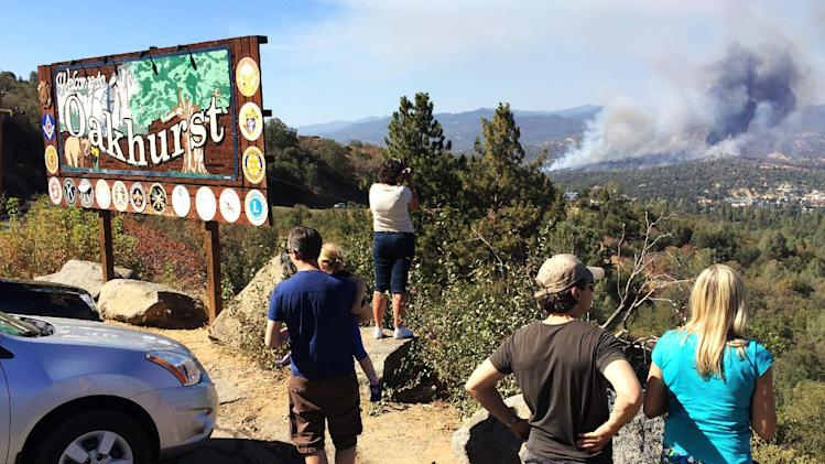 People watch a fire burning from the Highway 41 overlook on the way north into Oakhurst, Calif., Monday, Aug. 18, 2014. The fire is burning north of the community. (AP Photo/The Fresno Bee, Eric Paul Zamora)
