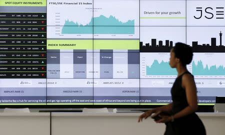 A worker walks past an electronic board displaying movements in major indices, at the Johannesburg Stock Exchange in Sandton
