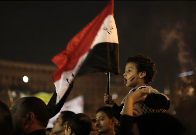 A young Egyptian boy waves a national flag from his mother's shoulders as protesters chant slogans in Tahrir Square in Cairo, Egypt, Tuesday, Dec. 4, 2012. A protest by tens of thousands of Egyptians 
