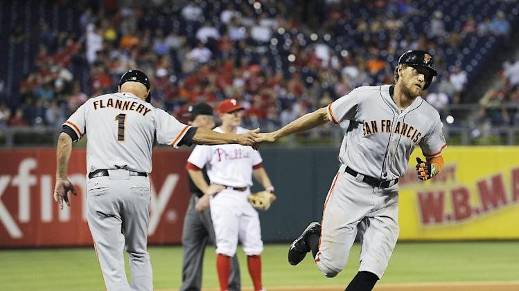 San Francisco Giants' Hunter Pence, right, is greeted by third base coach Tim Flannery after hitting a solo home run to center field in the fifth inning of a baseball game against the Philadelphia Phillies on Tuesday, July 22, 2014, in Philadelphia. (AP Photo/Michael Perez)
