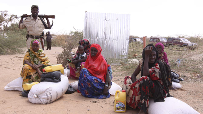 Somali women rest after receiving their food aid from UNHCR at the dollow refugee camp in southern Somalia on Tuesday. Aug. 30.2011.   Despite the drought and famine, refugees in Somalia are celebrating the Muslim holiday of Eid al-Fitr with the food rations distributed by aid agencies for their survival. (AP Photo/Khalil Senosi)