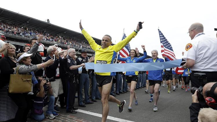 Joe Briseno, of springfield Ill., leads a group of the approximately 35 runners from the 2013 Boston Marathon, unable to finish the race due to the tragic bombings, to complete the distance by crossing finish line at the Indianapolis Motor Speedway before the start of the 97th Indianapolis 500 auto race. (AP Photo/Darron Cummings)