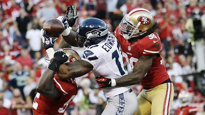 San Francisco 49ers linebacker Patrick Willis (52) and safety Dashon Goldson (38) break up a pass intended for Seattle Seahawks wide receiver Braylon Edwards (17) during the second quarter of an NFL football game in San Francisco, Thursday, Oct. 18, 2012. (AP Photo/Marcio Jose Sanchez)