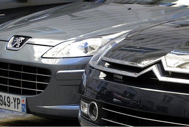 In this Sept. 7, 2012 file photo, a Peugeot, left, and Citroen cars are parked in Paris. PSA Peugeot Citroen posted Wednesday, Feb,13, 2013 a record Euro 5 billion ($6.7 billion) loss last year after 