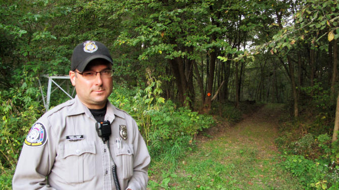 In this Sept. 18, 2012, photo Ed McCann, a warden with the Wisconsin Department of Natural Resources, stands near a property where the DNR caught someone suspected of digging wild ginseng root illegally. Law enforcement officials say the price of wild ginseng, which can be worth as much as $600 a pound, has pushed people looking for quick money, particularly the unemployed and drug addicts, into the woods, never mind permits, permission or preservation. (AP Photo/Carrie Antlfinger)